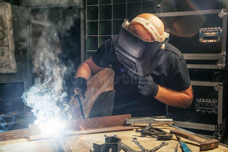 Mężczyzna warzy metal spawalniczą maszynę zdjęcia stock