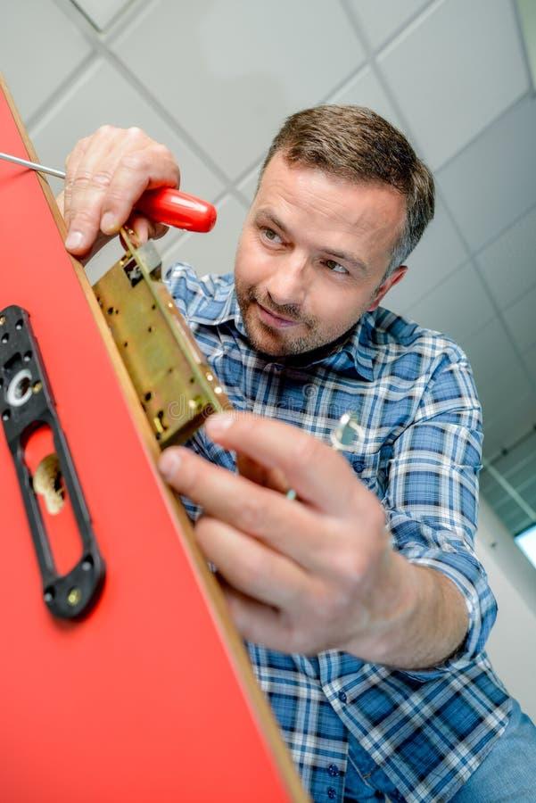Mężczyzna wkłada drzwiowego kędziorka mechanizm zdjęcia royalty free