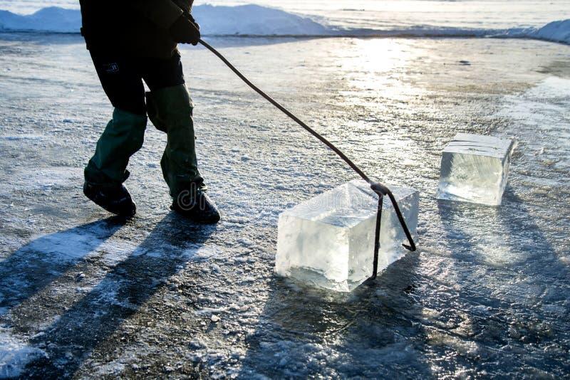 Mężczyzna wlec wielkiego blok piłujący rzeka lód pracownicy minują wielkich sześciany naturalny rzeka lód fotografia stock