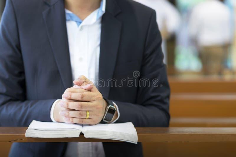 Mężczyzna wręcza modlenie na świętej biblii w kościół dla wiary pojęcia, duchowości i chrześcijanin religii, zdjęcie stock