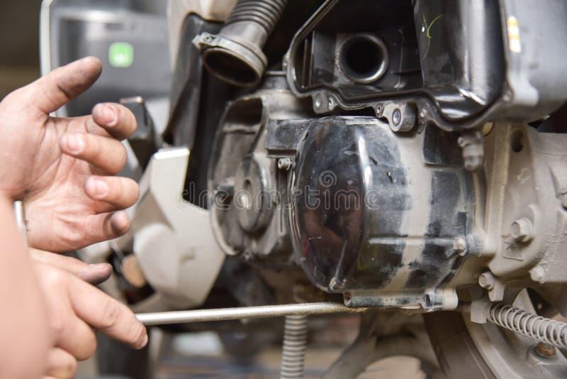 Mężczyzna wręcza naprawianie motocykl zdjęcia stock