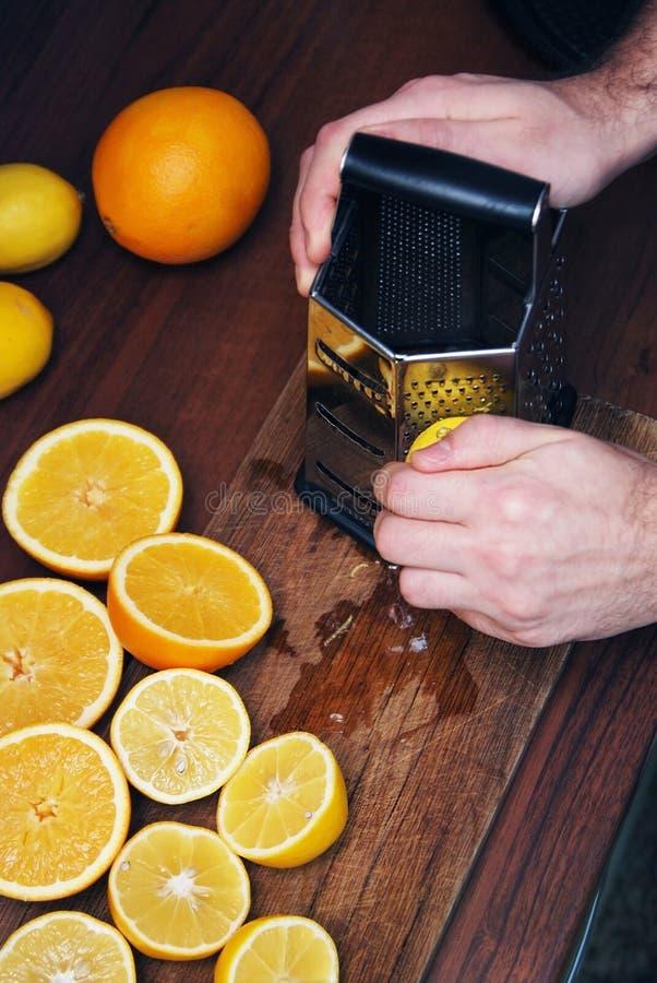Mężczyzna Wręczają barkentyny cytryny łupę dla cytryna torta Wiele przyrodnie Cutted cytryny, cytrus na zmroku stole i Karmowy i  obraz royalty free