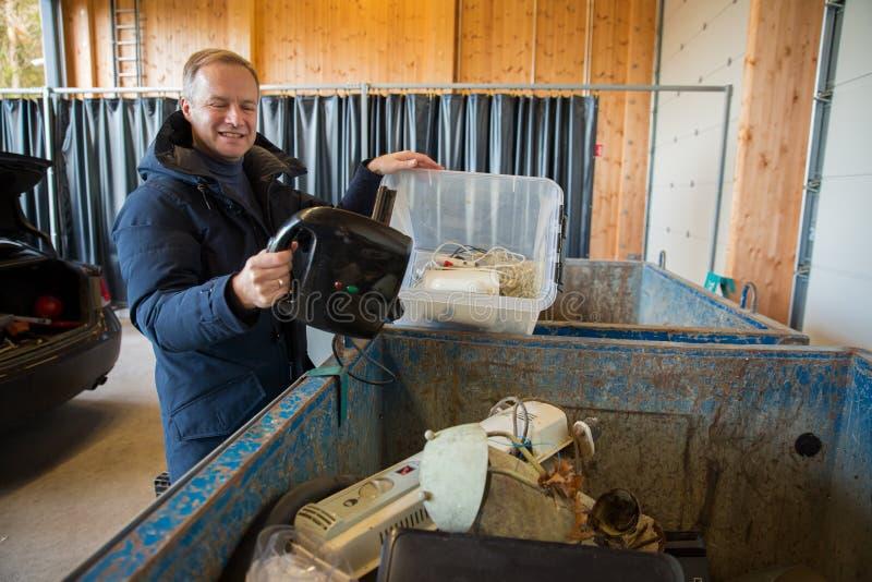 Mężczyzna wrzucający stare urządzenia do śmietnika obrazy stock