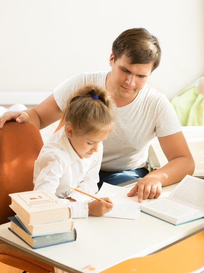 Mężczyzna wskazuje na błędzie przy córka notatnikiem obraz royalty free