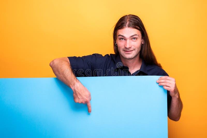 Mężczyzna wskazuje z pozytywną uśmiechniętą postawą sztandar zdjęcie royalty free