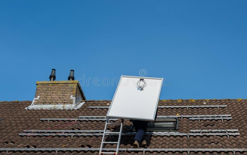 Mężczyzna wspina się drabinę z panelem słonecznym fotografia royalty free