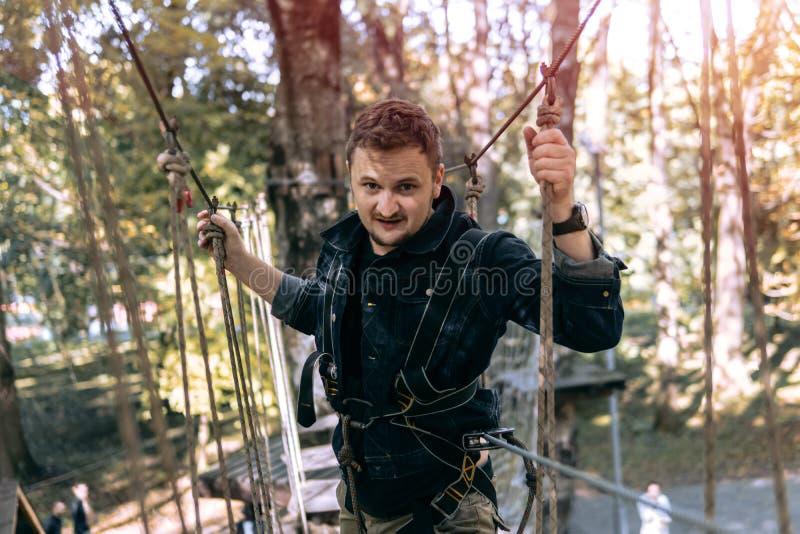 Mężczyzna, wspina się przekładnię w przygoda parku angażuje w rockowym pięciu lub przechodzi przeszkody na linowej drodze, arbore fotografia stock