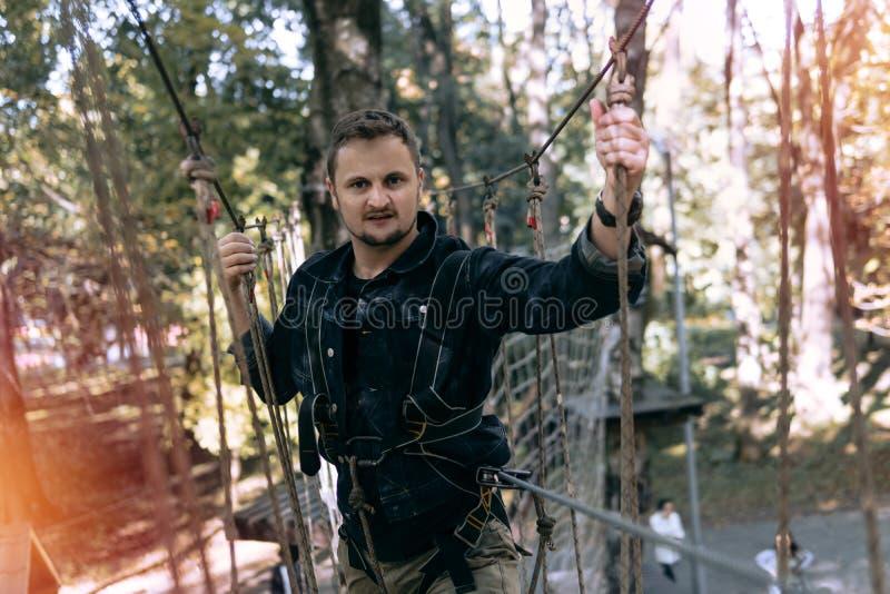Mężczyzna, wspina się przekładnię w przygoda parku angażuje w rockowym pięciu lub przechodzi przeszkody na linowej drodze, arbore fotografia royalty free