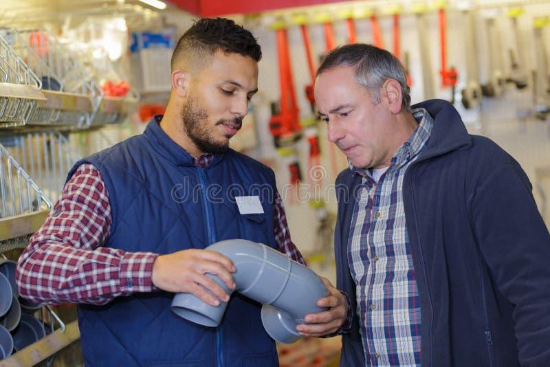Mężczyzna wybiera instalacj wodnokanalizacyjnych dopasowania od przechuje fotografia royalty free