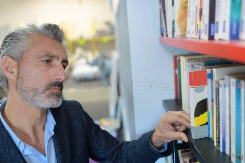 Mężczyzna wybiera książki w bibliotece obrazy royalty free