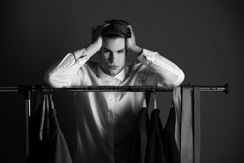 Mężczyzna wybiera kurtki i krawata zrozumienie na garderoba wieszaku fotografia stock