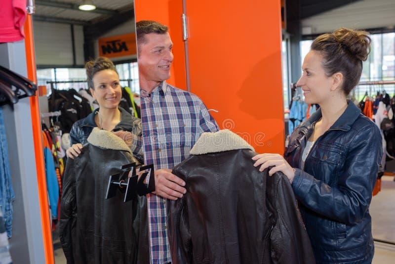 Mężczyzna wybiera skórzaną kurtkę w sklepie detalicznym obraz royalty free