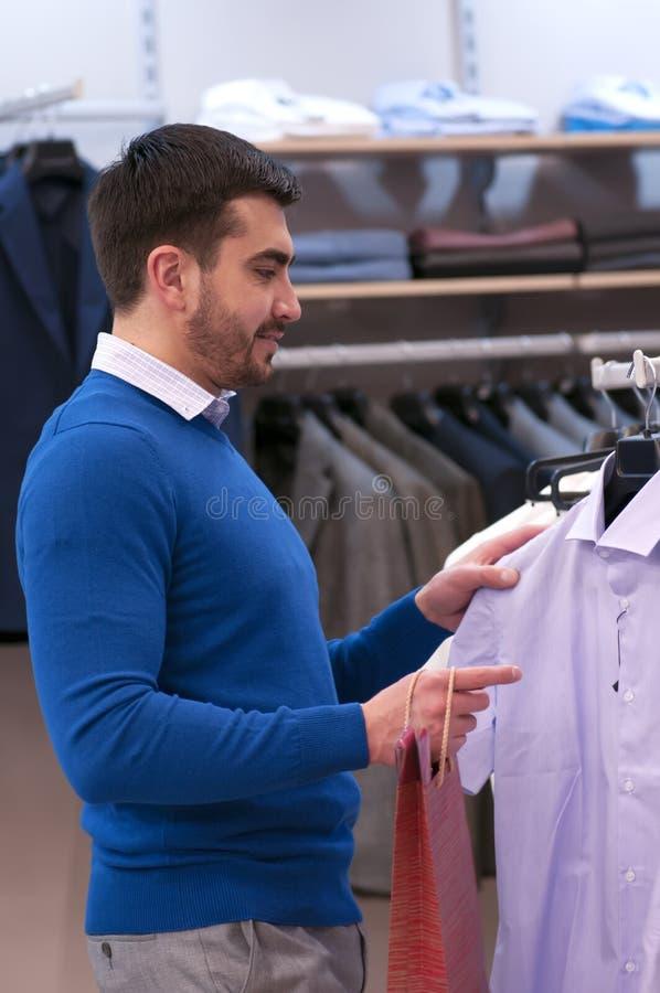 Mężczyzna wybiera trójnika - koszula przy sklepem obraz stock