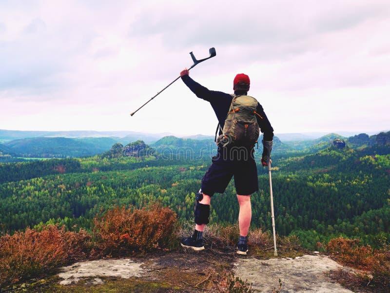 Mężczyzna wycieczkowicz Jest ubranym Wspierającego noga bras, gainst i cruthes Naturalny lasu park zdjęcia royalty free
