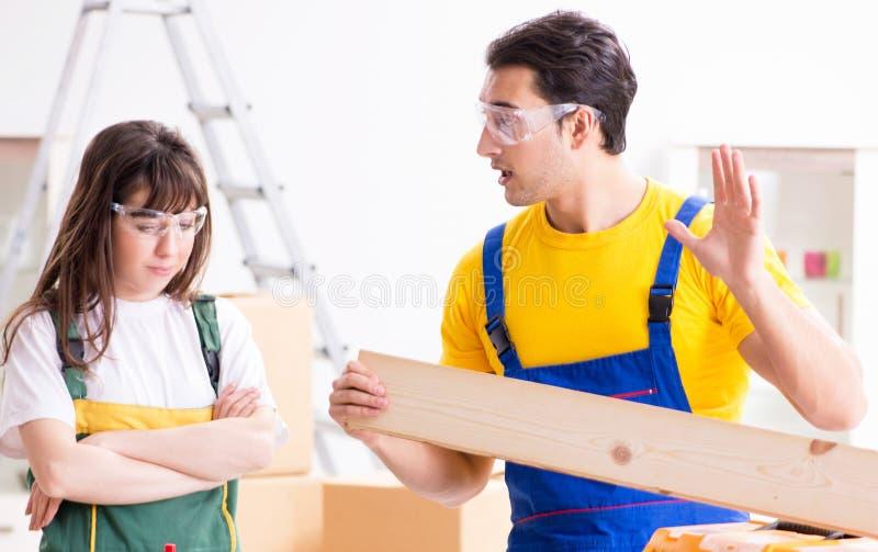 Mężczyzna wyjaśnia kobiety woodworking porady w drewnianym warsztacie obrazy royalty free