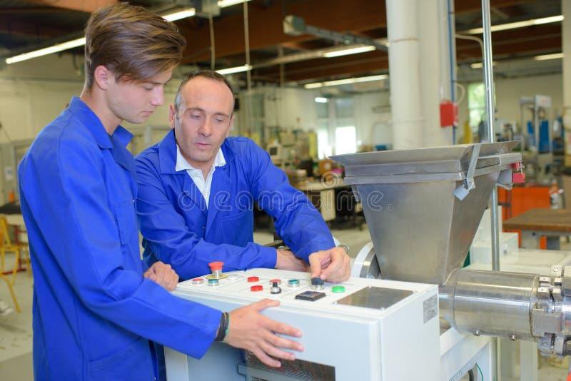 Mężczyzna wyjaśnia kontrola maszynowe młodzieżowy pracownik obrazy stock