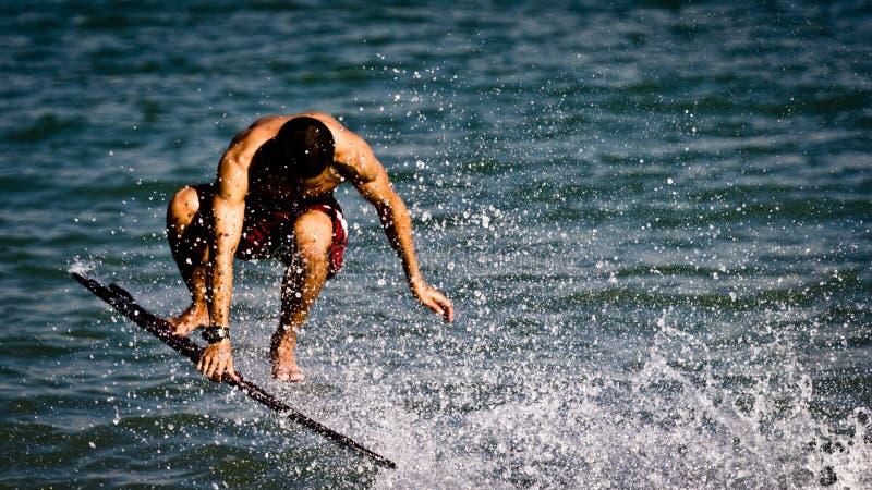 Mężczyzna wykonuje wyczyny kaskaderskich na jego surfboard obraz royalty free