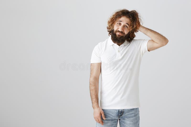 Mężczyzna wyraża jego zamieszanie i unawareness Portret atrakcyjny dorosły wschodni facet z kędzierzawym włosy i brodą zdjęcie stock