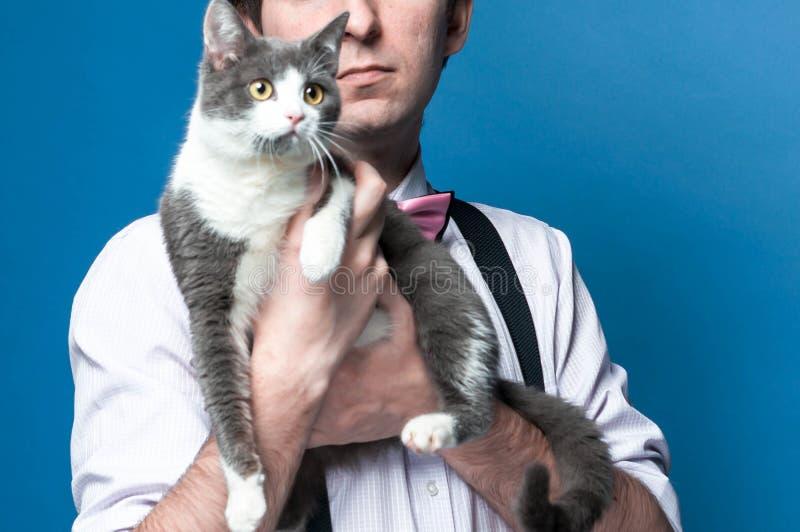 mężczyzna z ślicznym popielatym kotem na błękitnym tle zdjęcia stock