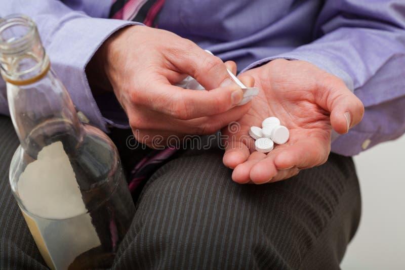 Mężczyzna z środkami przeciwbólowymi i alkoholem obraz stock
