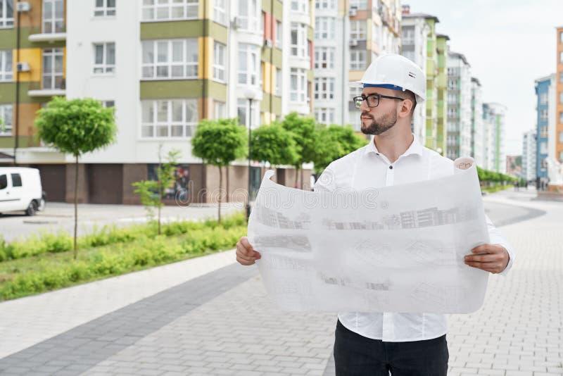Mężczyzna z architektonicznym projektem na papierowym patrzeje domu zdjęcia royalty free