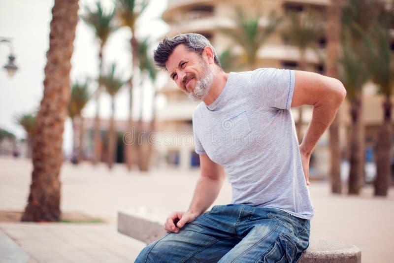 Mężczyzna z ból pleców obsiadaniem na ławce przy plenerowym Ludzi, opieki zdrowotnej i medycyny pojęcie, zdjęcie royalty free