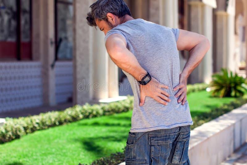 Mężczyzna z ból pleców przy ulicą Ludzi, opieki zdrowotnej i medycyny pojęcie, zdjęcia royalty free