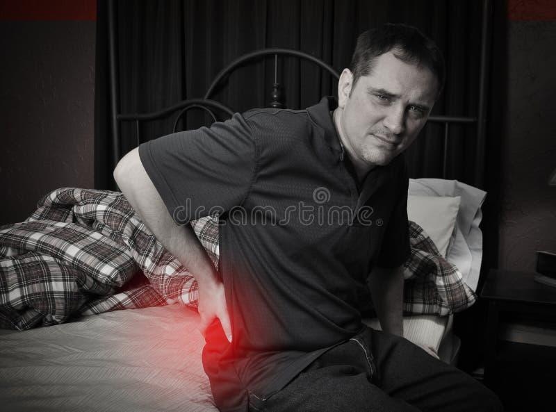 Mężczyzna z bólu pleców obsiadaniem na łóżku obraz stock