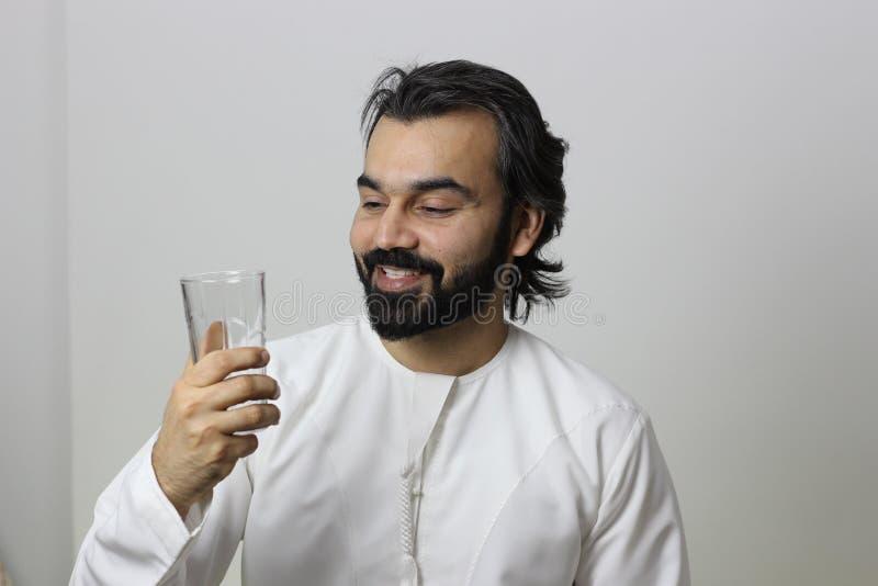Mężczyzna Z Bliskiego Wschodu Trzymający Szklankę Wody I Spoglądający W Szkło Bardzo Zadowolony zdjęcia royalty free
