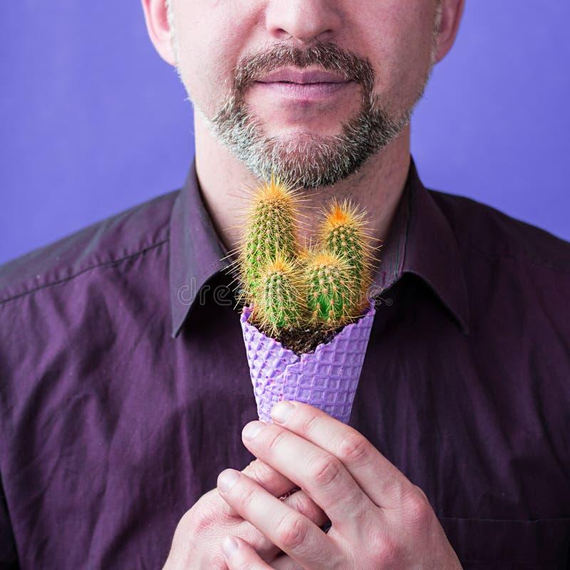 Mężczyzna z brodą z fiołkową lody kukurudzą z kaktusem w jego ręki zdjęcie stock
