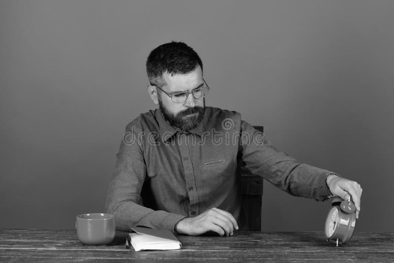Mężczyzna z brodą i szkłami sprawdza czasu mienia budzika obrazy stock