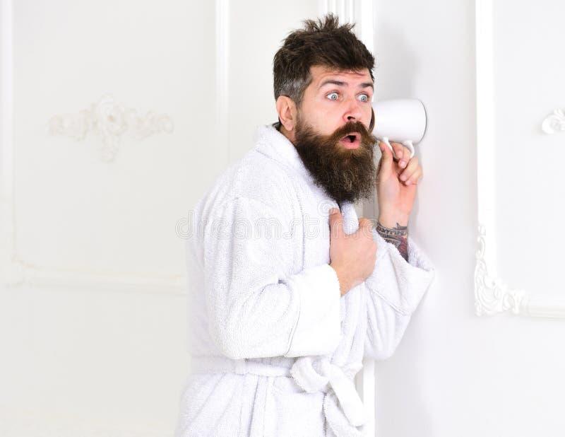 Mężczyzna z brodą i wąsy podsłuchuje używać filiżankę blisko izoluje Modniś w bathrobe na zdziwionej twarzy skrycie słucha obraz stock
