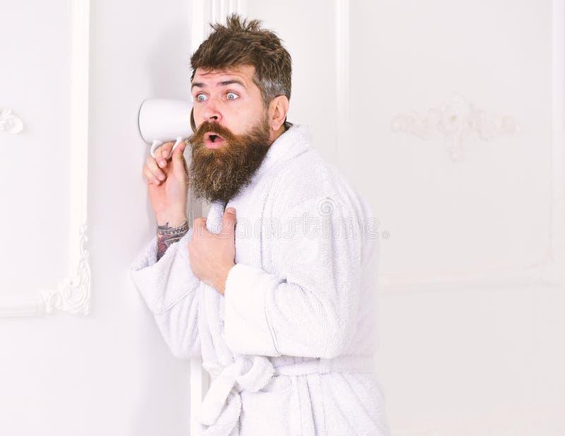 Mężczyzna z brodą i wąsy podsłuchuje używać filiżankę blisko izoluje Modniś w bathrobe na zdziwionej twarzy skrycie słucha obrazy stock