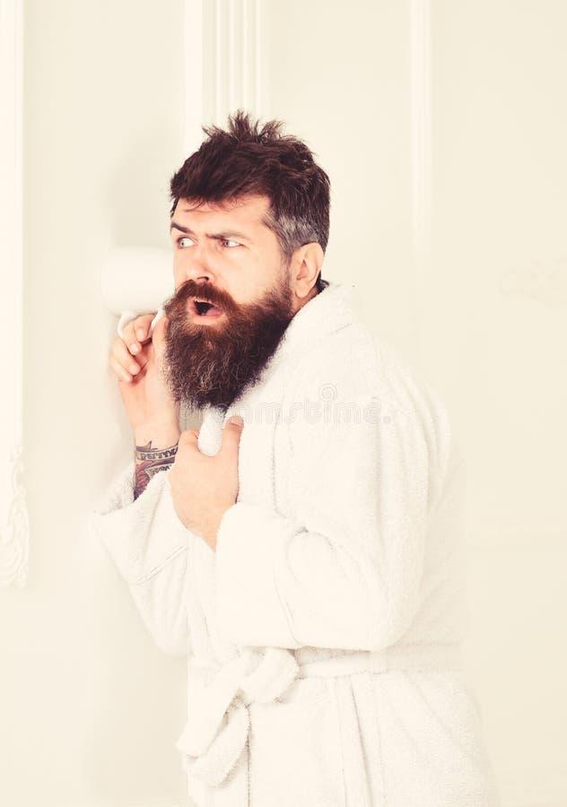 Mężczyzna z brodą i wąsy podsłuchuje używać kubek blisko izoluje Modniś w bathrobe na skoncentrowanej twarzy skrycie słucha obraz stock