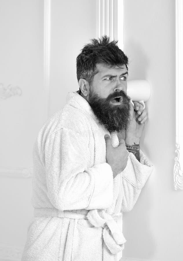 Mężczyzna z brodą i wąsy podsłuchuje używać kubek blisko izoluje Modniś w bathrobe na skoncentrowanej twarzy skrycie słucha zdjęcia royalty free