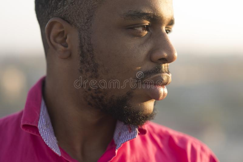 Mężczyzna z brodą i wąsy przy zmierzchem, miastowy tło, defocused Mężczyzna na spokój relaksującej twarzy, zamyka up Afrykanin za obrazy royalty free