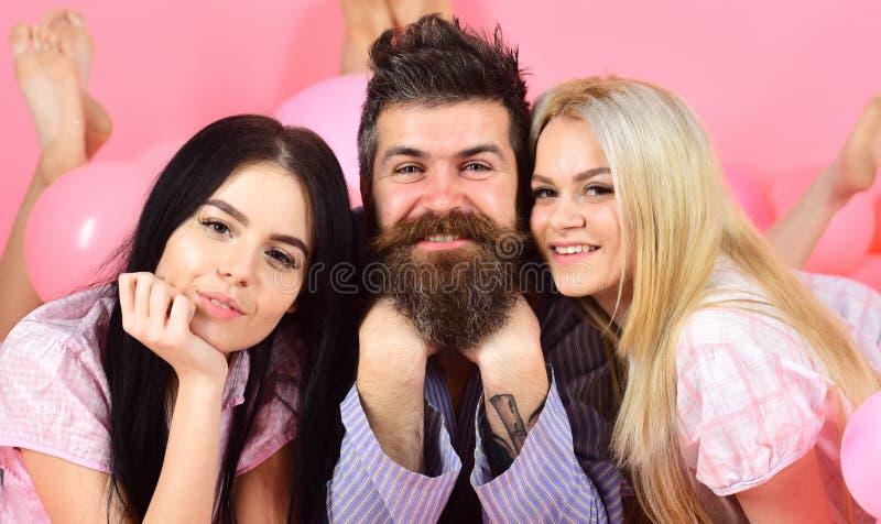 Mężczyzna z brodą i wąsy przyciąga blondynki i brunetki dziewczyny Dziewczyny spadają w miłości z brodatym macho, różowym tłem, obrazy royalty free