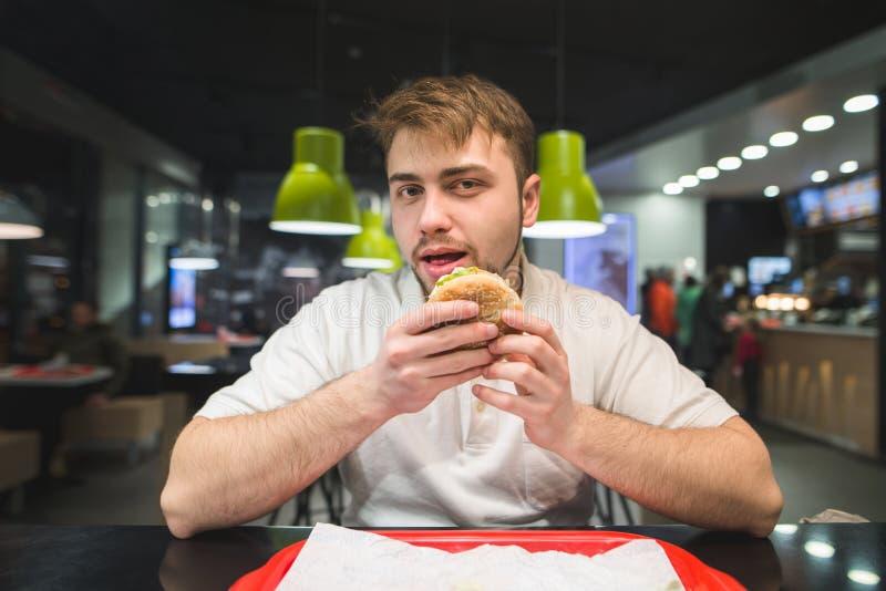 Mężczyzna z brodą siedzi w fast food restauraci z hamburgerem w jego spojrzeniach przy kamerą i rękach fotografia stock