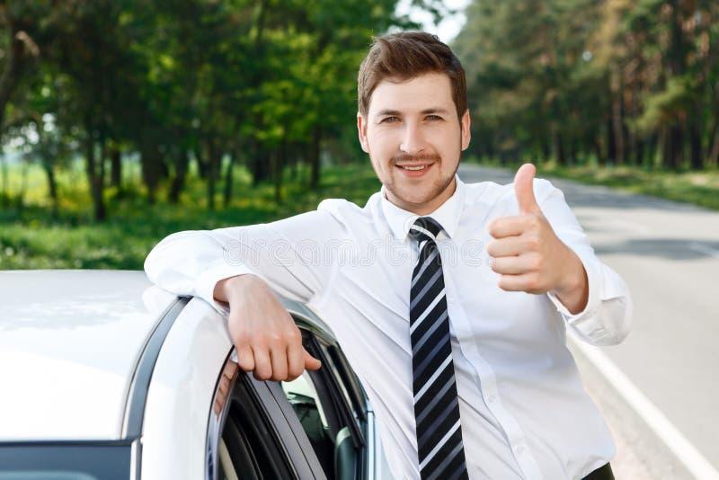 Mężczyzna z brodą thumbing w górę pobliskiego samochodu obraz stock