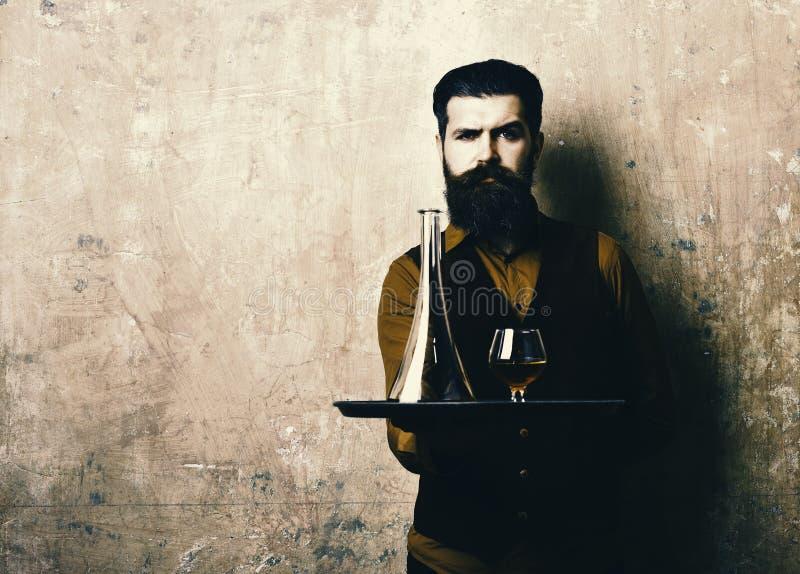 Mężczyzna z brodą trzyma koniaka na beżowym tle, kopii przestrzeń Usługa i restauracja napojów pojęcie Kelner z szkłem obrazy royalty free