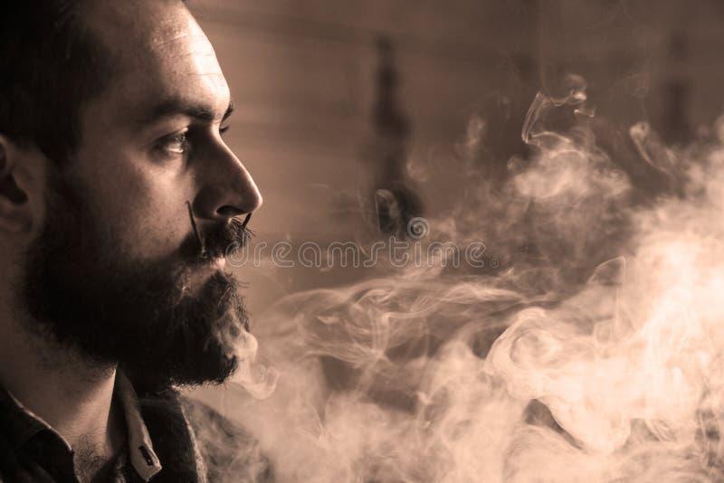 Mężczyzna z brodą Vaping i Mustages Elektroniczny papieros Vaper modnisia dymu odparowalnik i Exhals dymu pierścionki zdjęcie stock