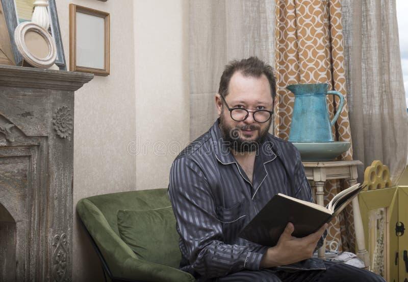 Mężczyzna z brodą w jego piżamach czyta książkę fotografia stock