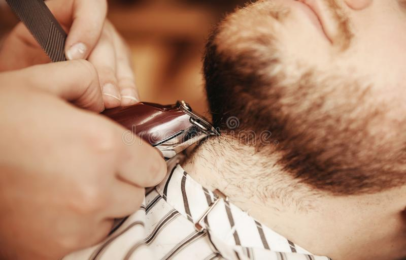Mężczyzna z brodą w zakładu fryzjerskiego fryzjera fryzjerze męskim na golenie żyletce obrazy royalty free