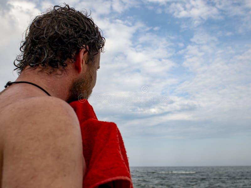Mężczyzna z brodą wyciera daleko ręcznika po pływać w morzu widok z powrotem fotografia royalty free