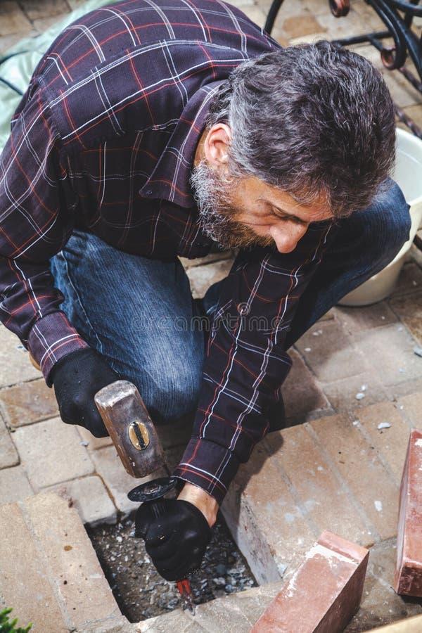 Mężczyzna z brod przerw kamieniarstwa ścinakiem i młotem zdjęcia royalty free