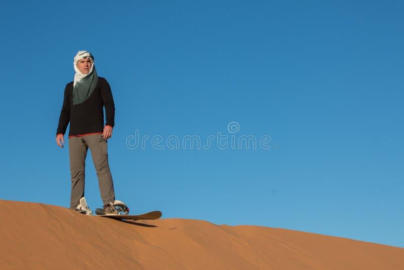 Mężczyzna z chustki na głowę ćwiczy sandboarding w pustynnych diunach erg Chebbi obrazy stock