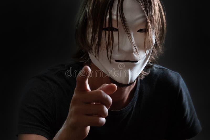Mężczyzna z długie włosy w anonimowej masce w koszulki stojakach z jego palcem naprzód lub hackerze Pojęcie sieka internet lub obraz royalty free