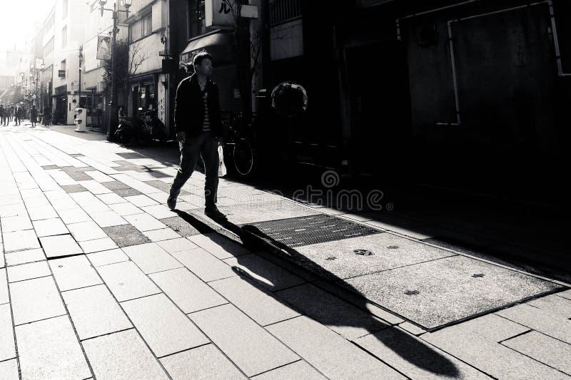 Mężczyzna z długim cieniem chodzi wzdłuż ulicy Japonia zdjęcia stock