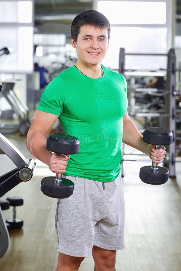 Mężczyzna z dumbbells robi ćwiczeniom w gym fotografia royalty free