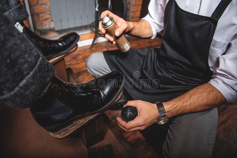 Mężczyzna z fartucha mienia kiścią przed butami obrazy royalty free